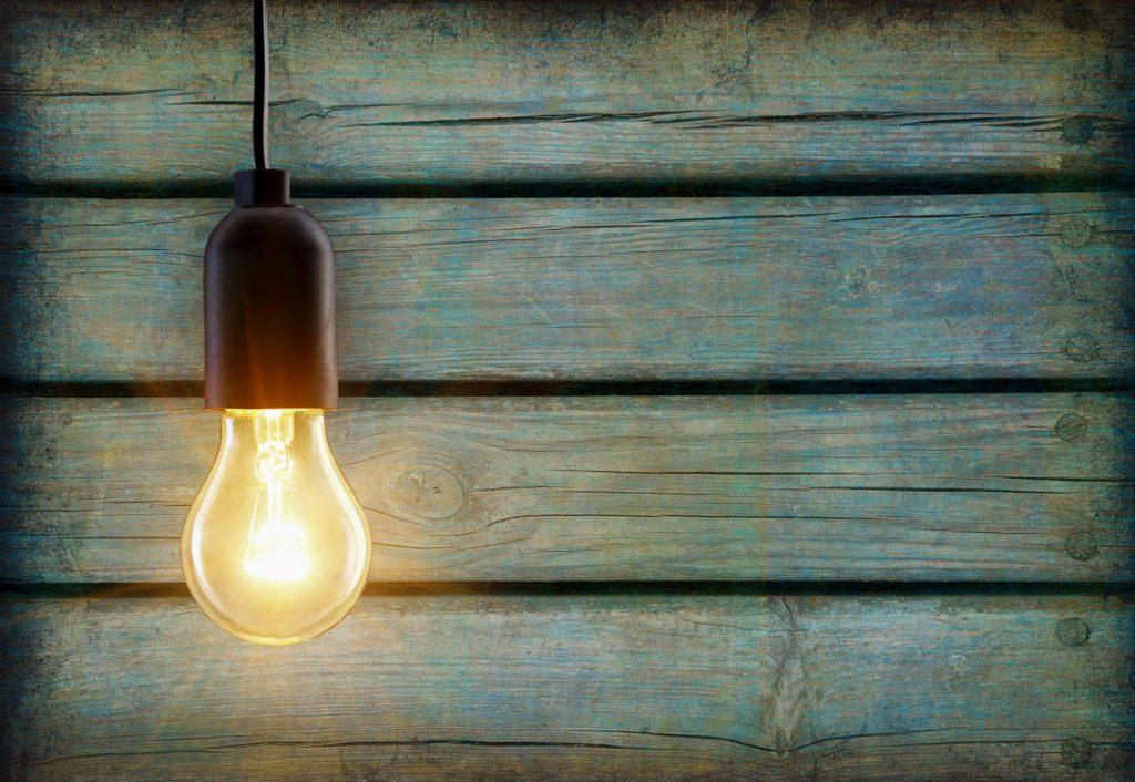 Lit up light bulb against treated wood slats.