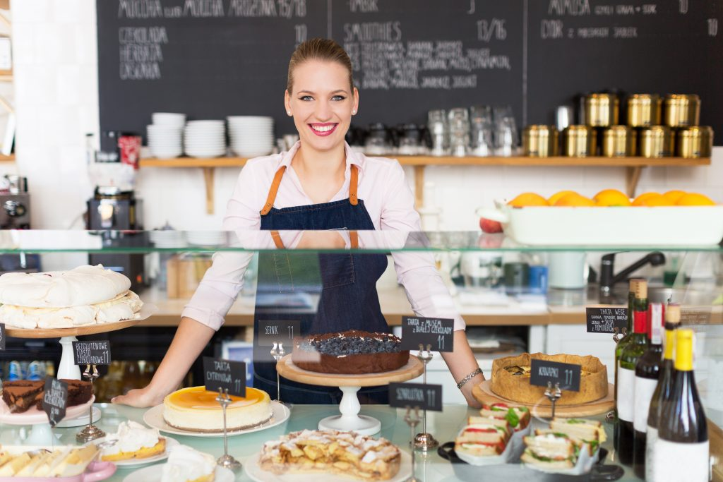 Female cafe owner standing behind the counter and smiling.