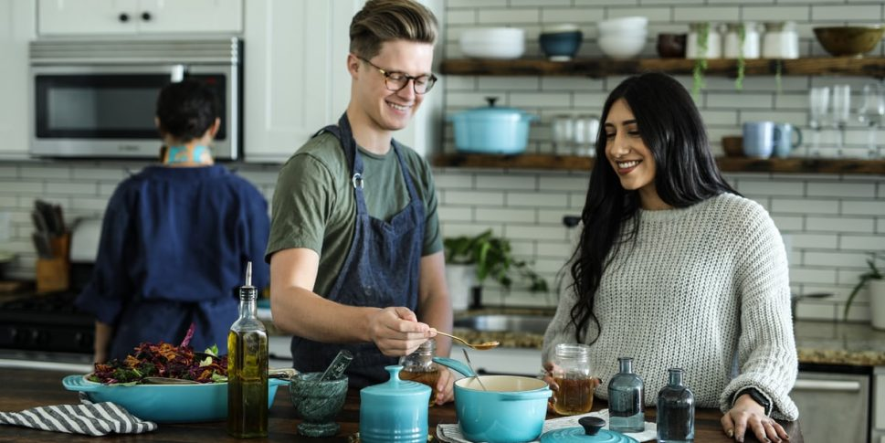 Three people in a commercial kitchen cooking.