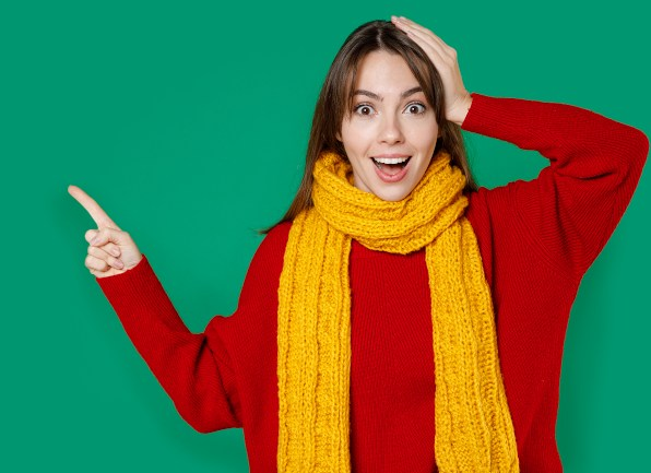 Woman in winter wear pointing at energy deal.