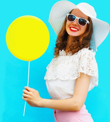 Woman holding balloon outside in the sunshine.