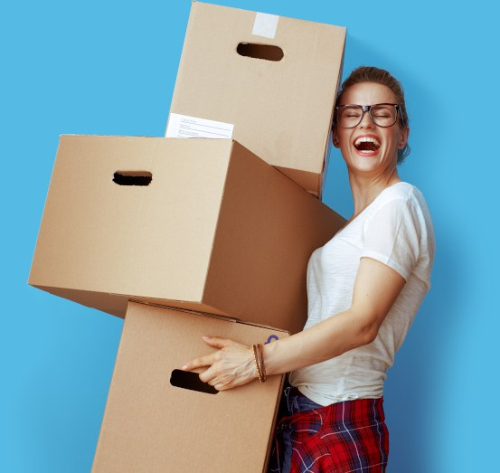 Woman carrying boxes as she moves home.