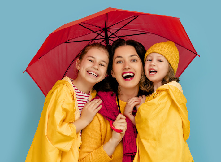 Mum with her two children under an umbrella.