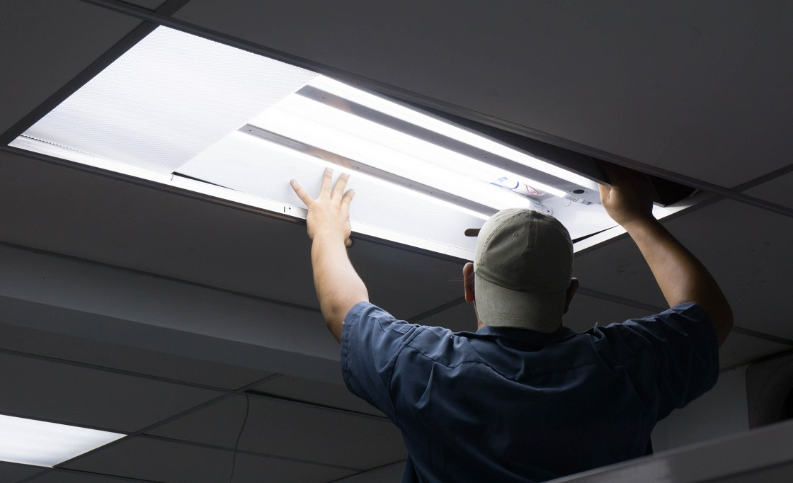 Man checking light as part of business energy saving tips.